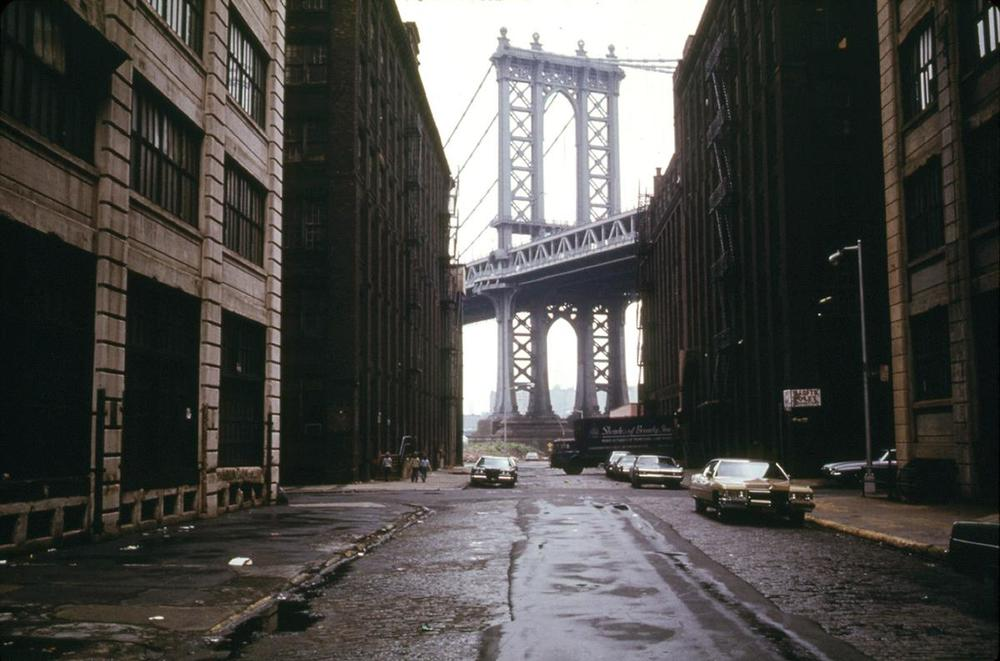 Manhattan Bridge tower in Brooklyn, New York City, framed through nearby buildings, in June of 1974.   Photo: Danny Lyon / National Archives and Records Administration. See this same spot today on  Google Street View .