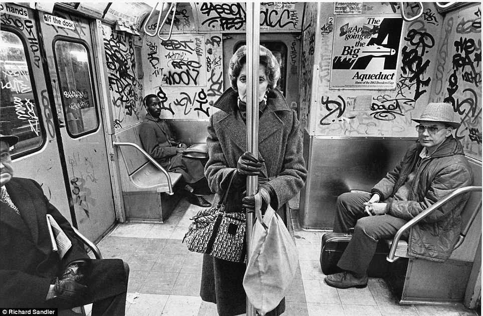 A woman stands in the graffiti-covered carriage of the C train in 1985 as other commuters look on. (Photo: Richard Sandler)