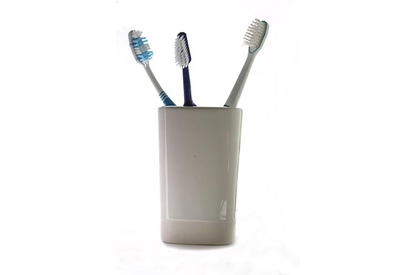 A toothbrush jar is the best option for storage, and they are inexpensive. You don't have to worry about touching other brushes either.