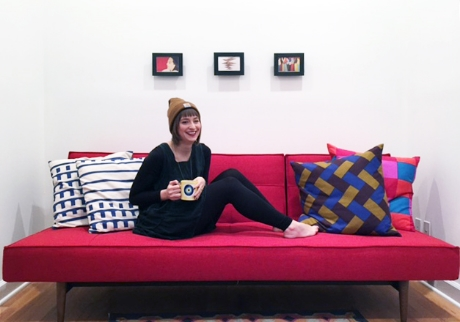 [Image of a woman smiling on a red couch with three black postcard frames above.]