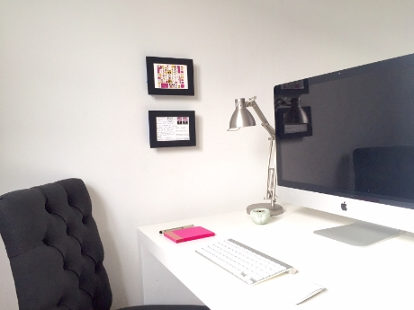 [Image of two shift frames vertically aligned on the wall next to an iMac on a white desk with a black tufted side chair.]
