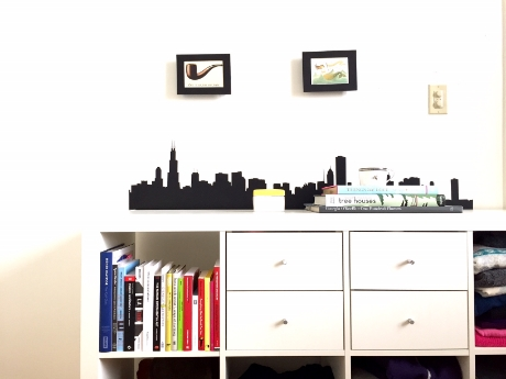 [Image of two shift frames horizontally aligned above a white cubed bookcase with a black Chicago skyline decal.]