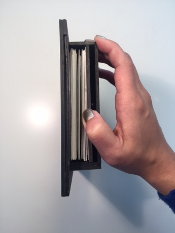 [Image of shift frame in profile view. The side is exposed with a hand holding back a board to expose forty stacked postcards.]