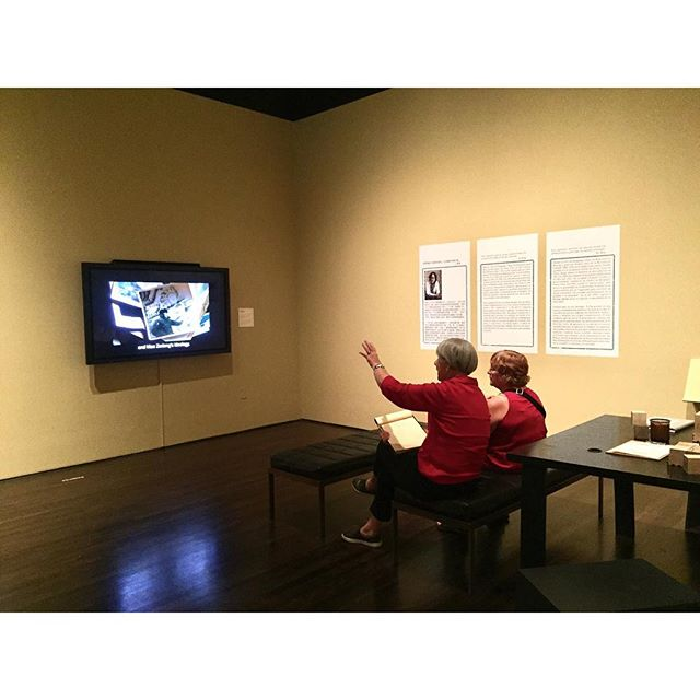 Seating in front of videos are rarely a bad idea. Besides places of rest, benches are also an invitation to stay. Here, one woman who was on the guided tour explains some of #XuBing's methodology to another woman who arrived after the tour concluded. @blantonmuseum  #MuseumSeating #TakeASeat #NoMoreMuseumFatigue #LadiesInRed