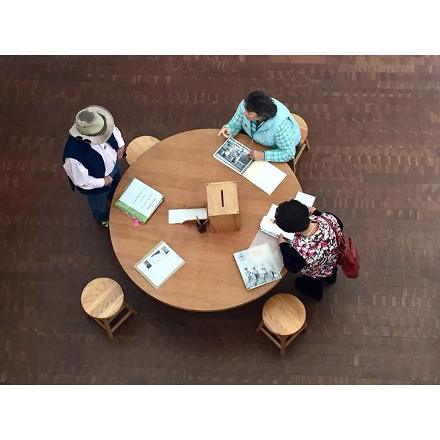 Activity table with stools in use in the Uprooted exhibition @jamuseum. Here, the museum asks visitors to for help identifying people photographed in the show. #TakeASeat #MuseumSeating #CrowdsourcingHistories