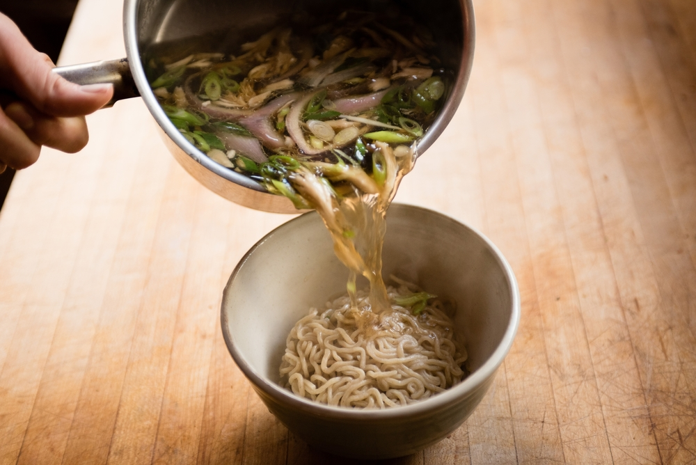 Pouring homemade chicken broth over Umi Organic fresh organic ramen noodles