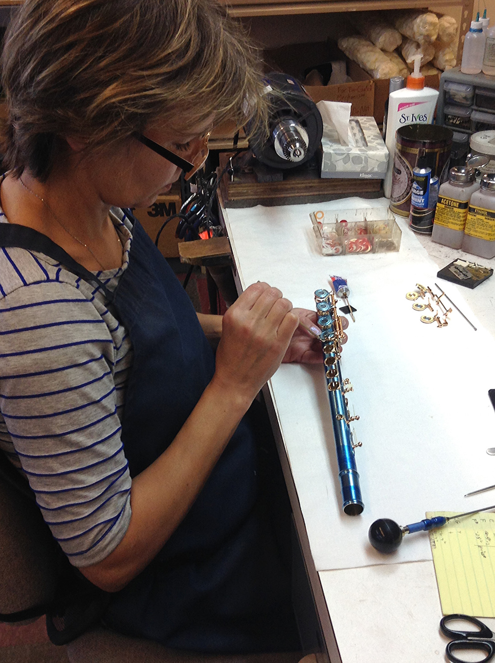 Galina at Powell, padding a flute with protective blue film