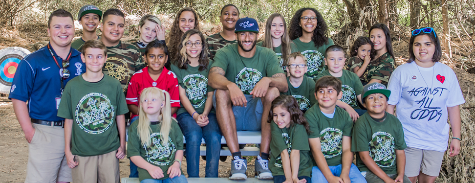Kaepernick (middle in blue hat) spending his time volunteering with Camp Taylor, an organization that helps children with cardiac issues. Photo via Camp Taylor website
