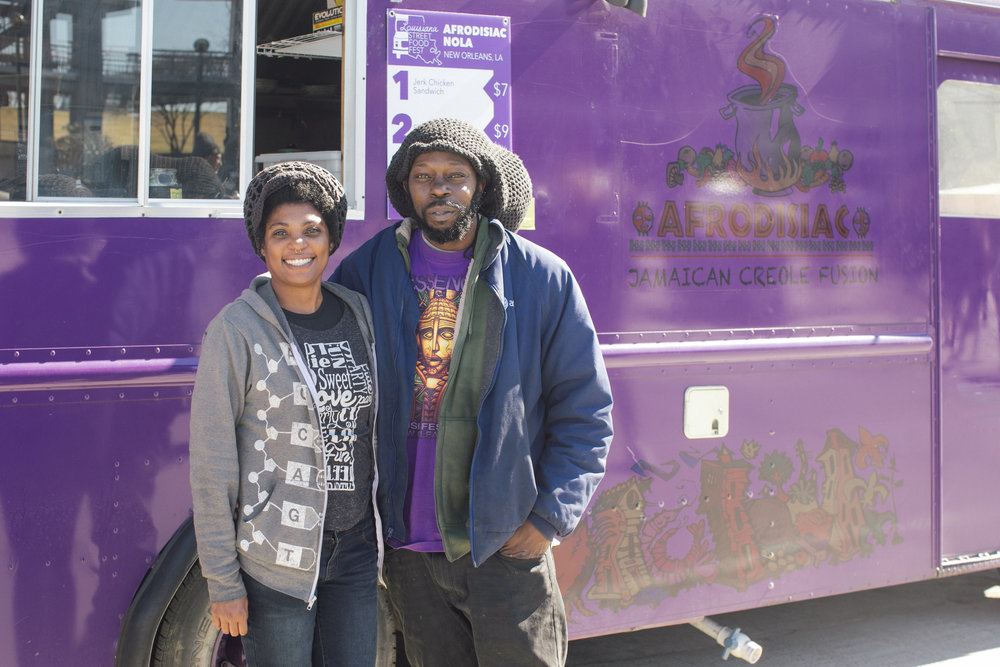 The husband and wife duo behind Afrodisiac NOLA smile in front of their purple truck. Afrodisiac NOLA serves unique fusion dishes combining flavors of Caribbean and New Orleanian cuisine.  OA