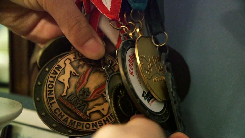 Marathon Men_Thomas showing medals .jpg