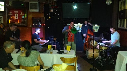 Sometime jazz faculty Andrew Speight (at bar) and Michael Zisman (seated, foreground), attend a performance by their sometime San Francisco State University students Mark Davis (trombone), Alex Farrell (bass), and Austin Lee Harris (drums). SFSU alumna and drummer Lilian Wu is talking with Michael; New Jersey visitor Ian House is on keyboards. (Photo by Jeff Kaliss)