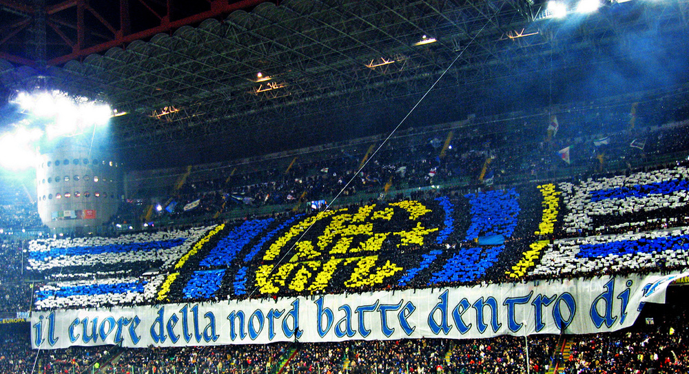 Fans of Inter Milan make the club crest out of coloured placards, and drape a banner reading 'Il cuore della nord batte dentro di te', which roughly translates into 'the heart of the North beats inside you'. Image credit: Oscar/Flickr