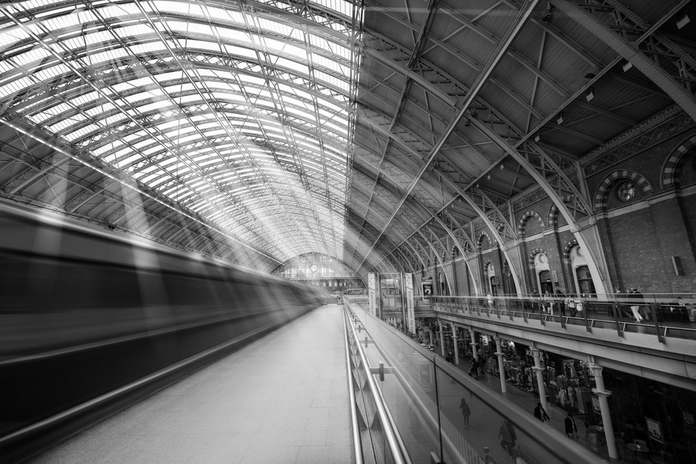 A black and white motion shot of a Eurostar leaving London St Pancras International Station.