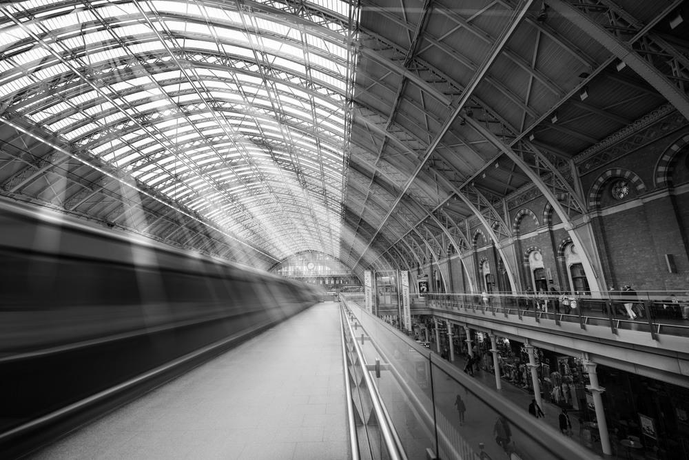 A black and white motion shot of a Eurostar leaving London St Pancras International Station.