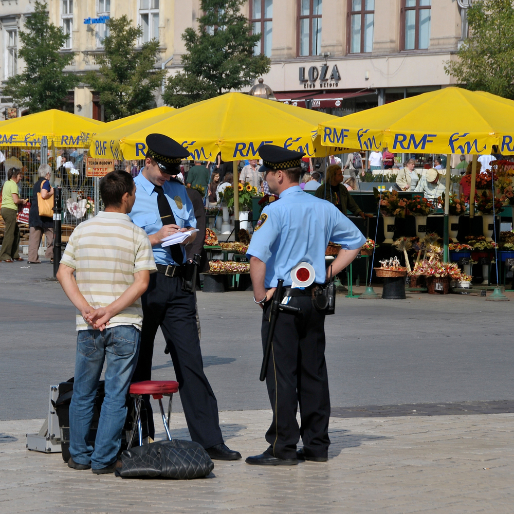 Polish policemen look like they're booking someone in Main Square. Image credit:  FaceMePLS /Flickr