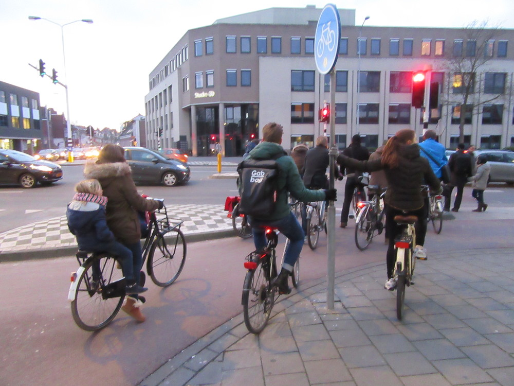People wait in the cycle lane to cross the road in Eindhoven.