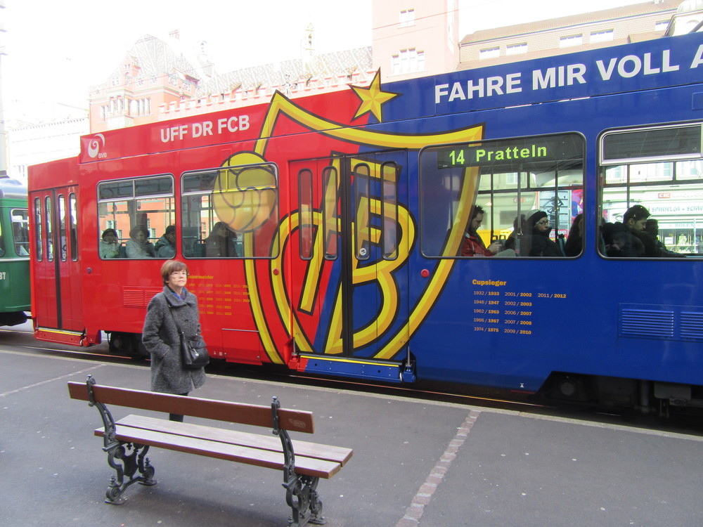 A tram with the front car adorned in the colours of the city's football team - FC Basel.