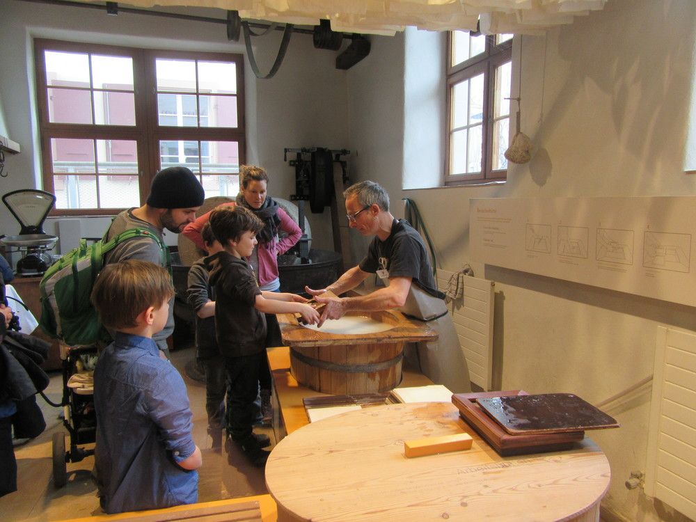 Children learning how to make paper at the museum.