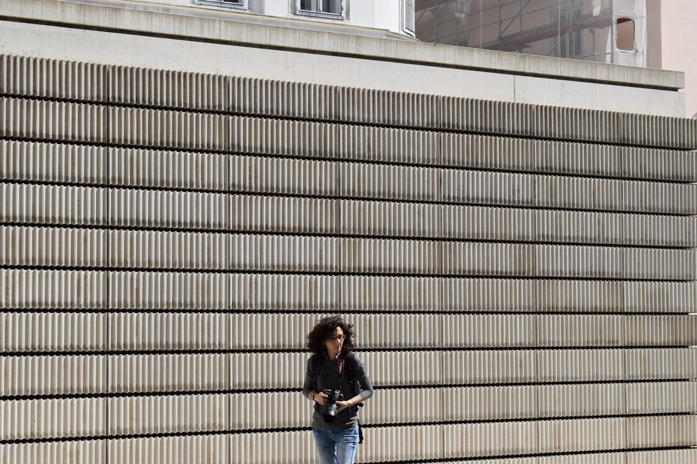 A photographer walks away from Judenplatz Holocaust Memorial after taking some snaps of her own.