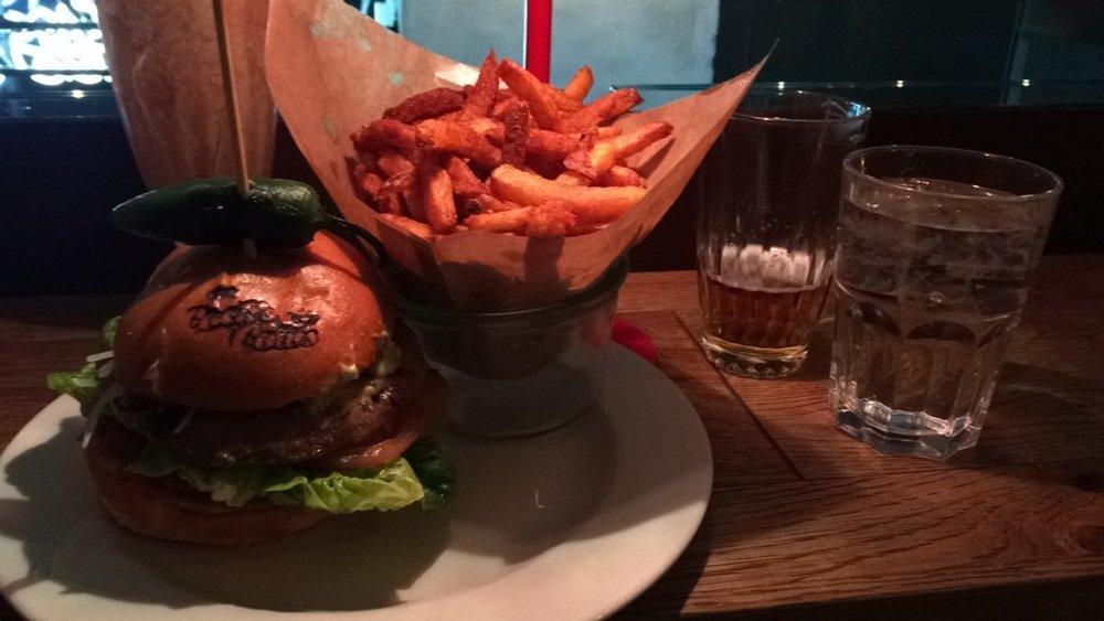 Enjoying a burger, fries and a drink at Cocks & Cows Copenhagen.