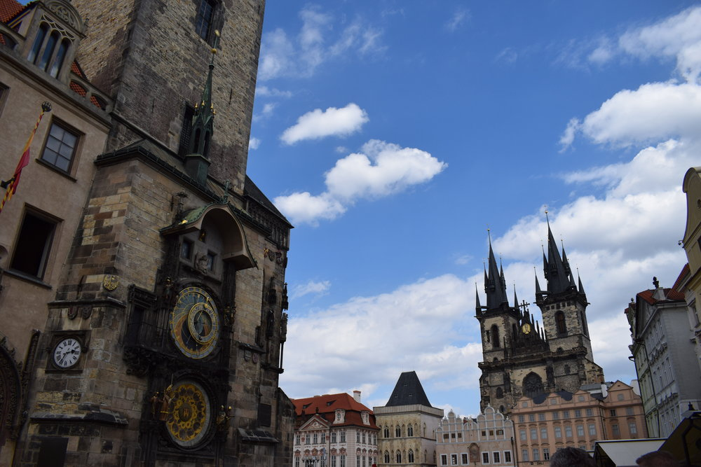 The Prague astronomical clock on the left of this image, while Church of Our Lady before Týn stands on the right.
