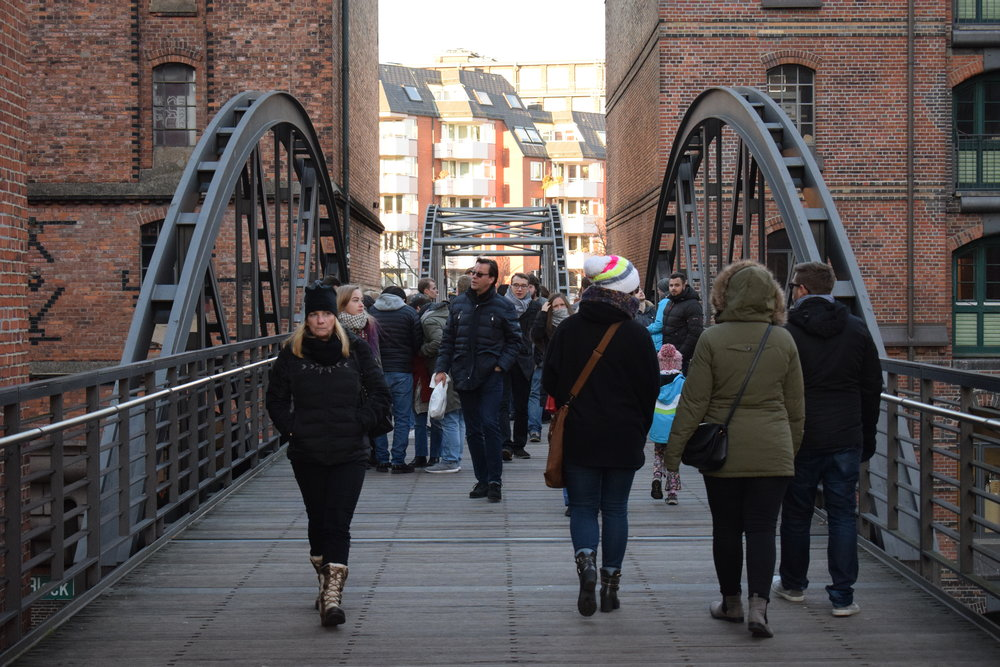 Tourists and locals alike enjoy views from a Speicherstadt bridge on a cool afternoon in the city.