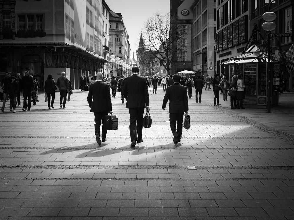 Three businessmen on their way to work. Image credit:    Bernd Zube   /   Flickr