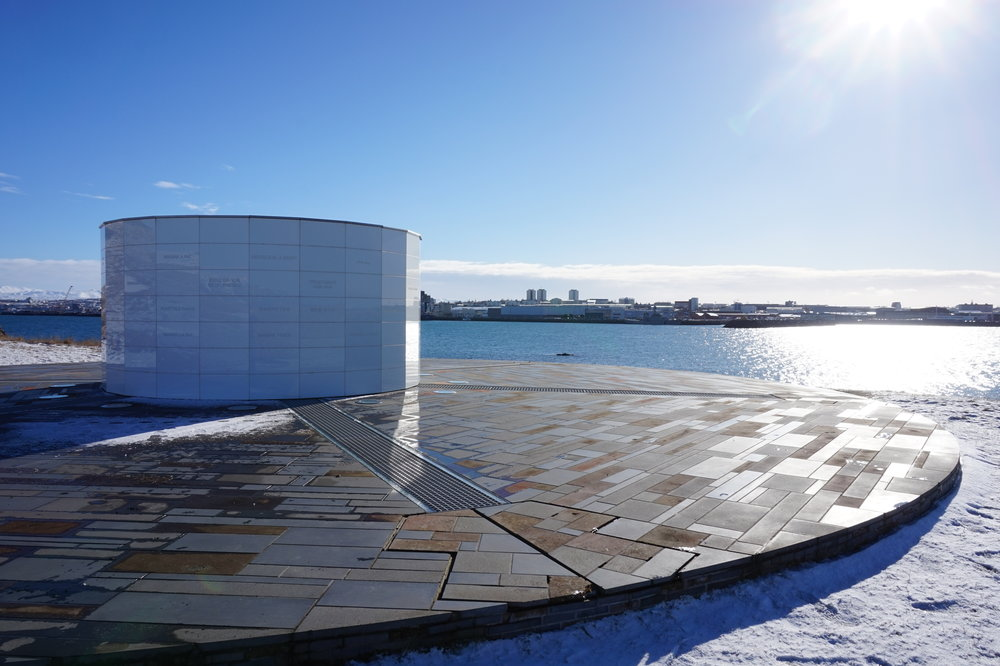 The Imagine Peace Tower looks across the water to a sunny Reykjavík.