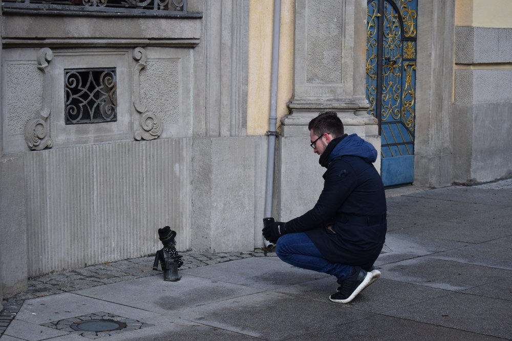A tourist taking a photo of a dwarf.
