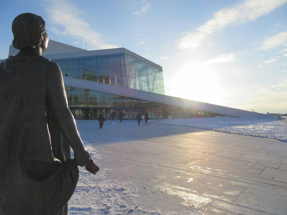A statue looks towards the Oslo Opera House.