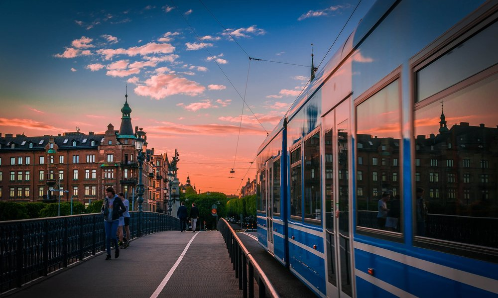 A tram going across a bridge as the sun sets over Djurgårdsbron in Stockholm. Image credit:  Tommie Hansen / Creative Commons