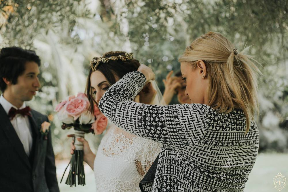 Hair and makeup artist helping bride on wedding day