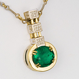 Eighteen karat two tone necklace featuring a 4.95-carat oval emerald (oil & resin) prong set with 0.23-carat diamonds on a handmade two tone chain. See Inv.#17858.