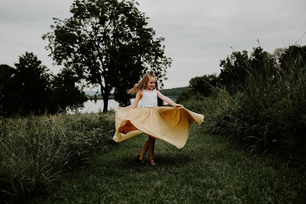 Young girl in boho skirt spinning in a grass field