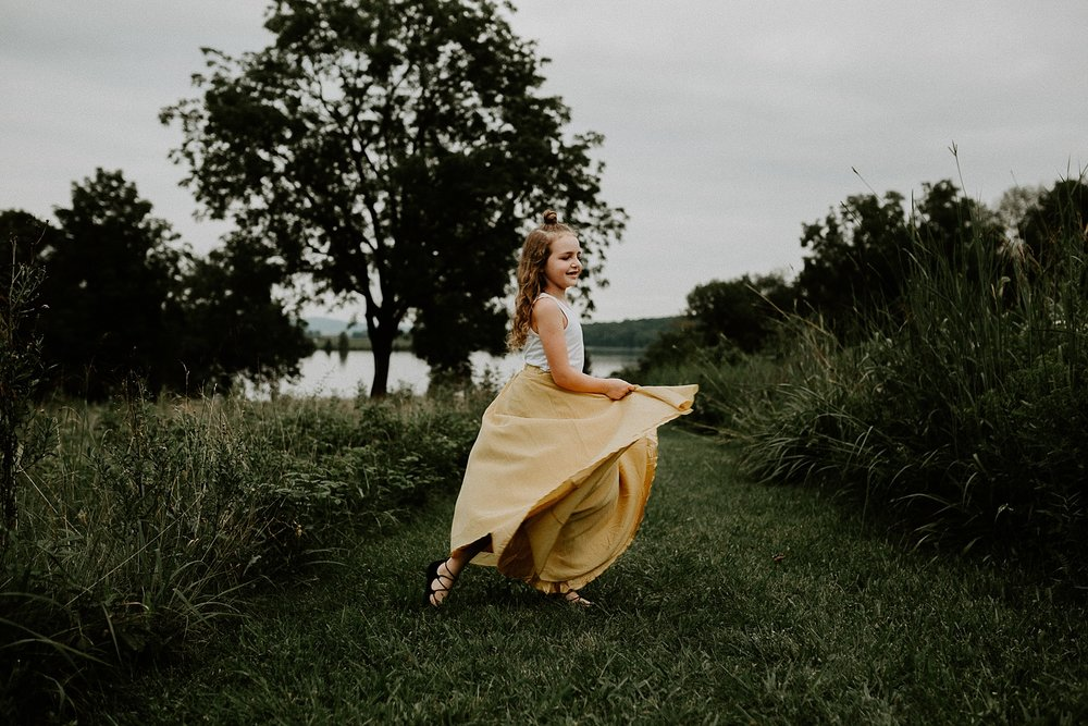 young girl twirling her skirt in grass field