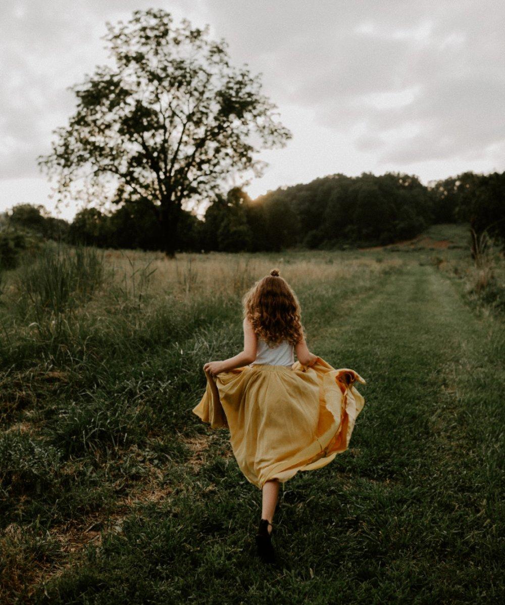 young girl running through grass field at sunset