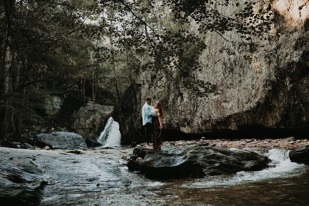 couple standing on rocks in front of waterfall