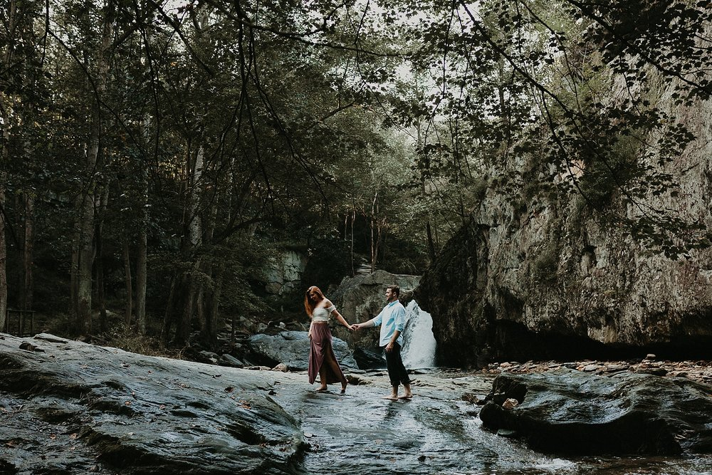 couple walking on top of rocks in front of waterfall