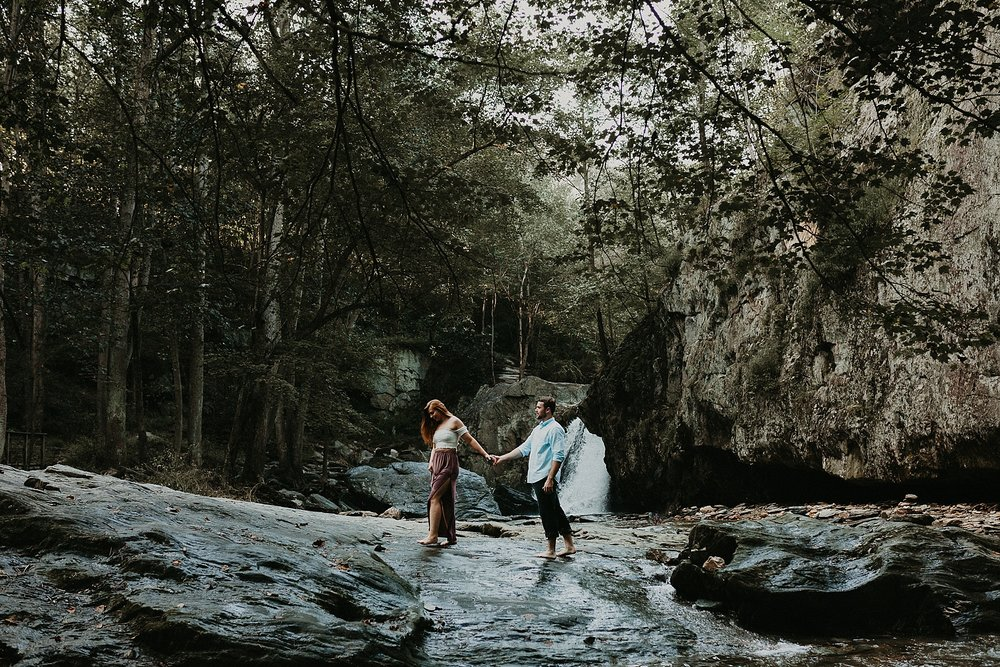 couple walking hand in hand on rocks