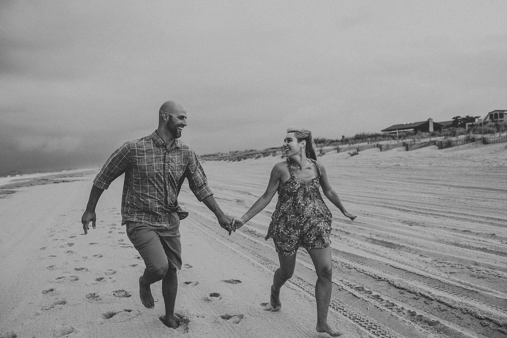 Couple running together on beach in Stone Harbor New Jersey