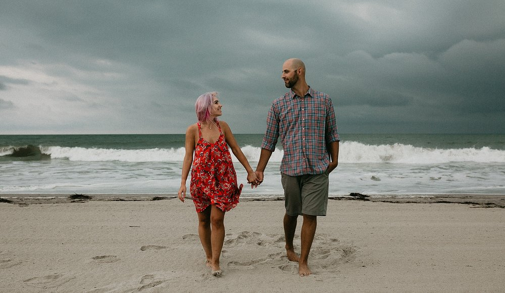 Couple walking towards camera while holding hands during Stone Harbor beach engagement session