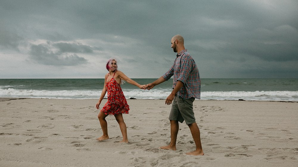 Couple walking on beach during engagement photos at Stone Harbor beach