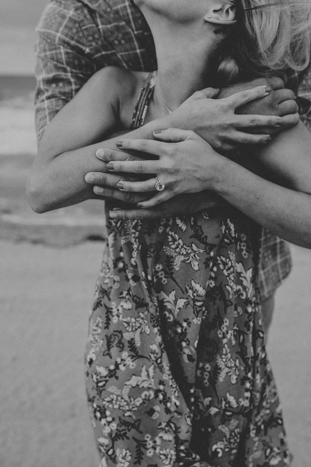 Couples hands and arms wrapped around one another during engagement photos on Stone Harbor beach in New Jersey