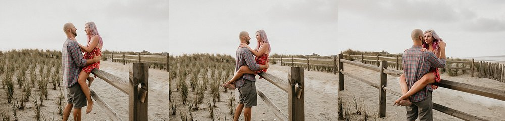 Girl on fence being held safe by fiancee during Stone Harbor beach engagement session