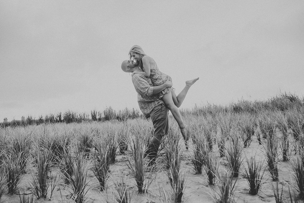Girl being lifted in boys arm for a kiss on sand dunes in Stone Harbor New Jersey