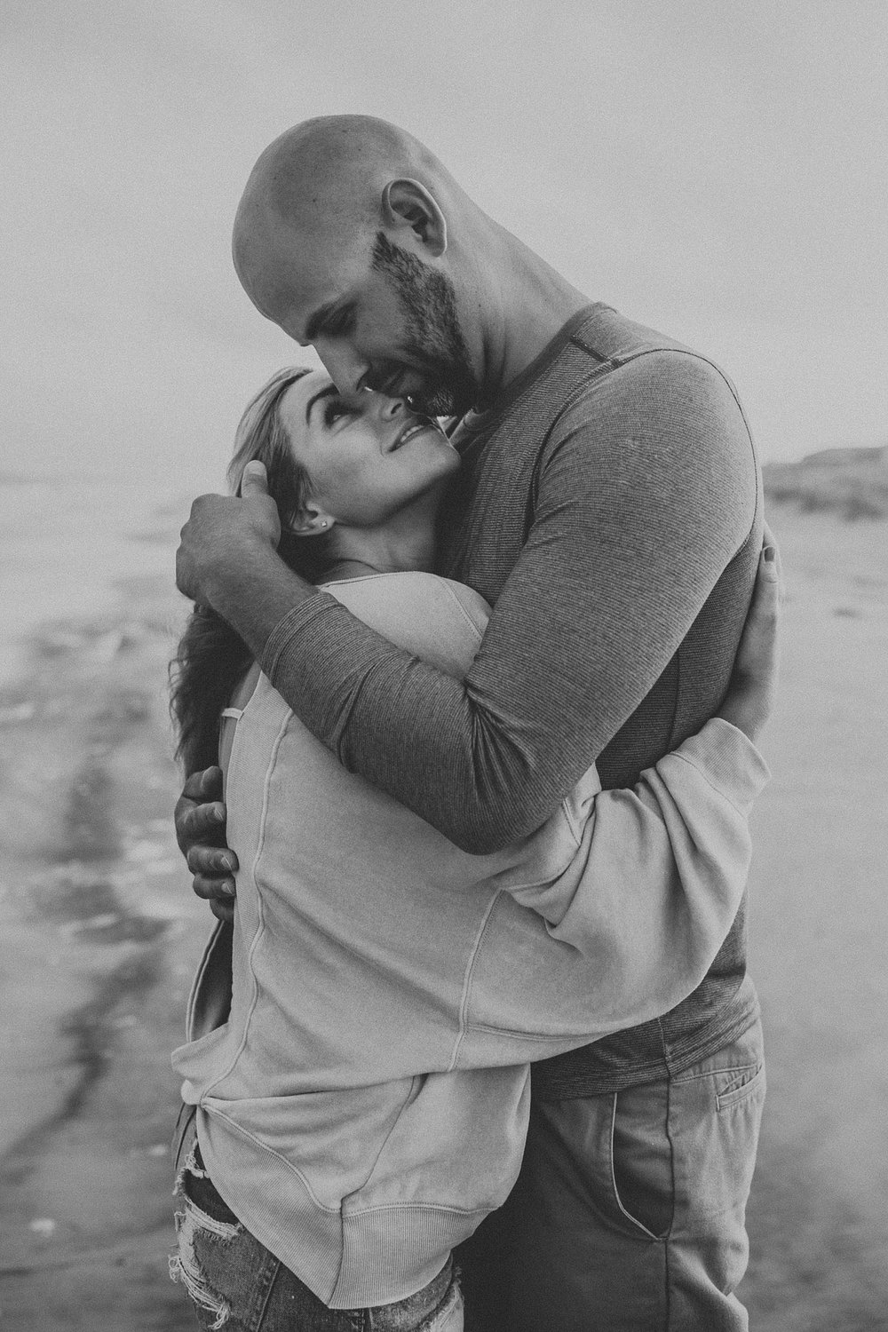 Couple wrapped up in arms keeping warm during windy Stone Harbor beach engagement session