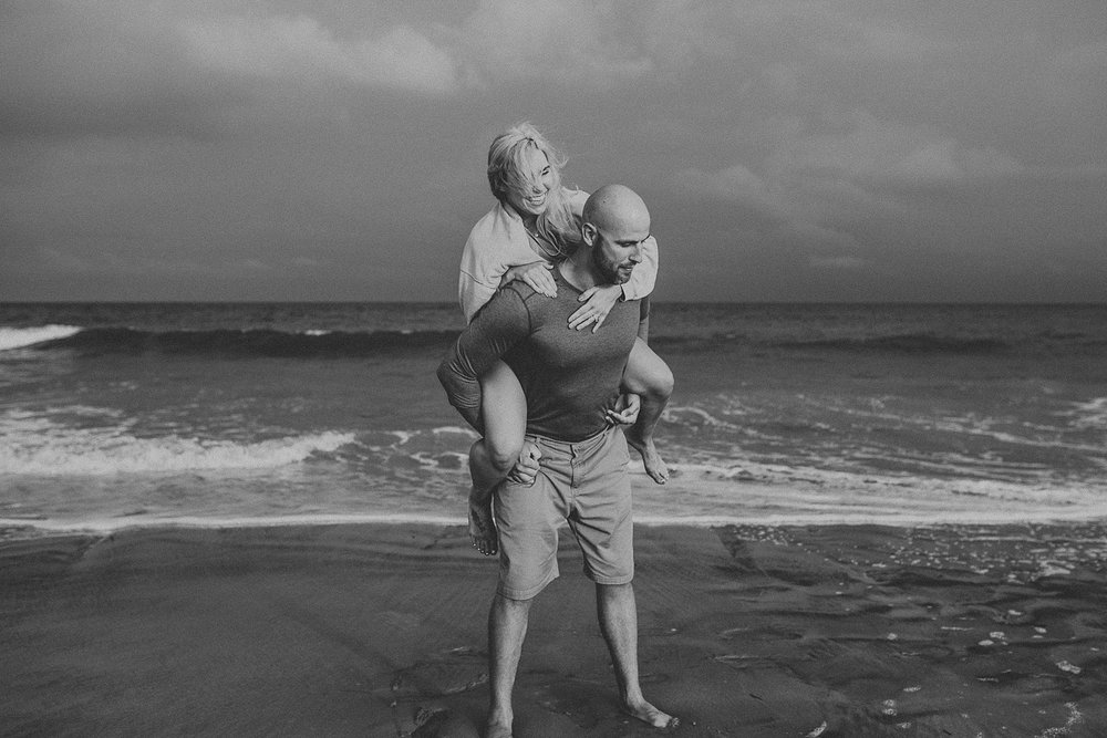 Running around beach on piggy back during engagement photos in Stone Harbor Beach New Jersey