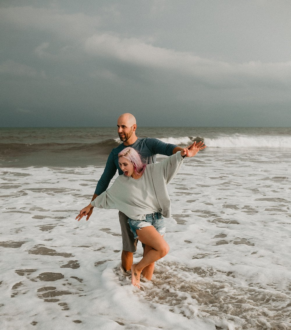 Couple splashing in ocean during engagement photos in Stone Harbor beach New Jersey