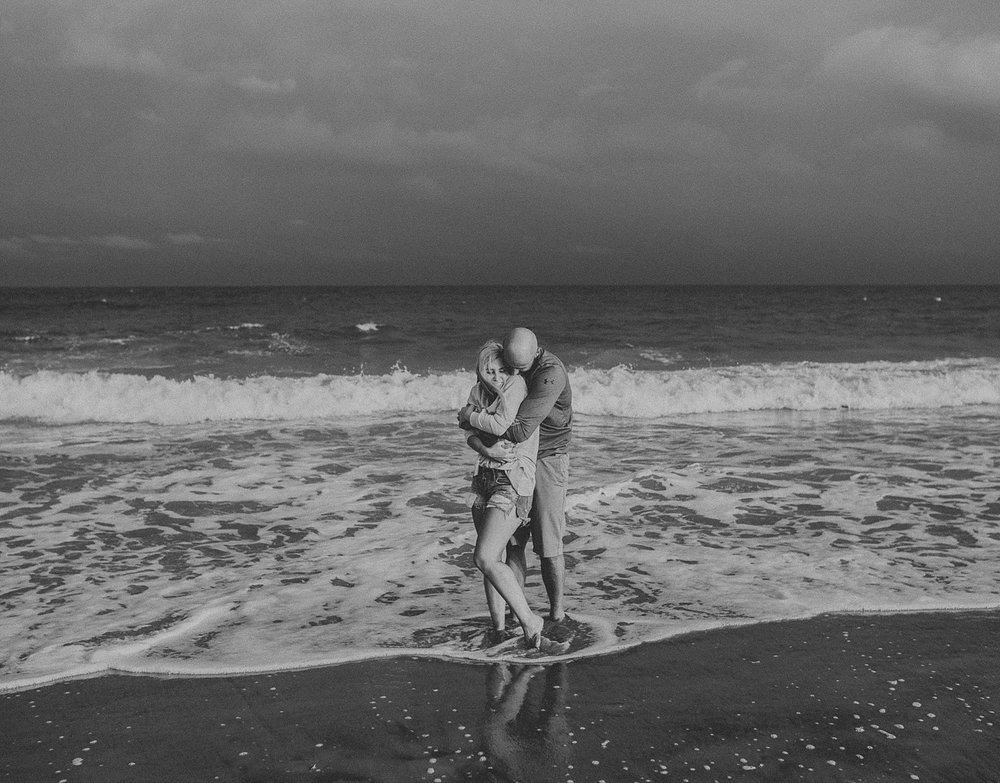 Couple running around and splashing in ocean during engagement photos in Stone Harbor New Jersey