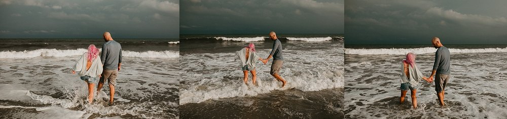 Couple playing in ocean during engagement photos in Stone Harbor beach New Jersey